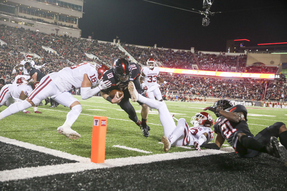 Photo - Oklahoma Sooners linebacker Curtis Bolton (18) hits Texas Tech Red Raiders quarterback Alan Bowman (10) while he attempts to score a touchdown during the NCAA football game between the Texas Tech Red Raiders and the Oklahoma Sooners at Jones AT&T Stadium in Lubbock, Texas on Saturday, November 03, 2018. IAN MAULE/Tulsa World