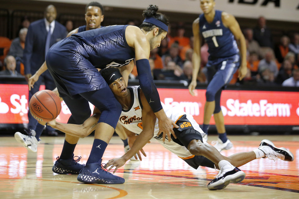 Photo - Oklahoma State's Avery Anderson III (0) tries to pass the ball from under Georgetown's Omer Yurtseven (44) during a college basketball game between the Oklahoma State University Cowboys (OSU) and the Georgetown Hoyas at Gallagher-Iba Arena in Stillwater, Okla., Wednesday, Dec. 4, 2019. [Bryan Terry/The Oklahoman]