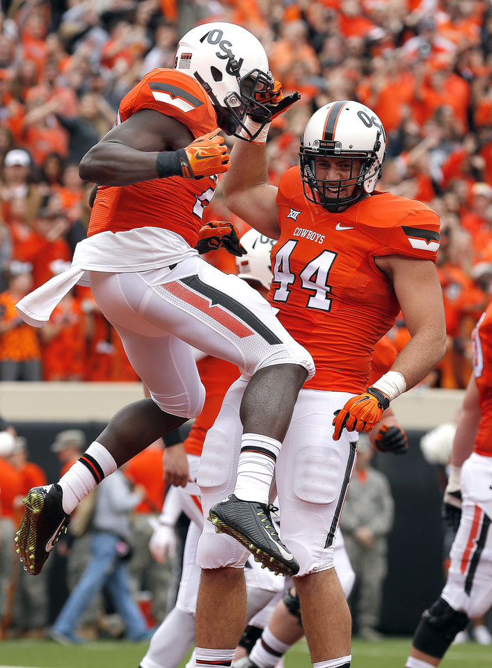 Photo - Oklahoma State's James Washington (28) and Jeremy Seaton (44) celebrates a Washington touchdown during a college football game between the Oklahoma State University Cowboys (OSU) and the Kansas Jayhawks (KU) at Boone Pickens Stadium in Stillwater, Okla., Saturday, Oct. 24, 2015. Photo by Sarah Phipps, The Oklahoman
