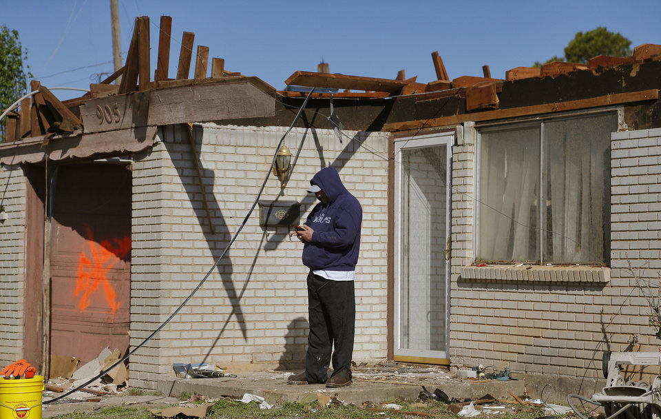 Photo - A resident stands outside a home that had its roof destroyed Storm damage in Moore, Okla. on Thursday, March 26, 2015. A tornado hit the area on Wednesday evening causing damage in the area.  Photo by Chris Landsberger, The Oklahoman