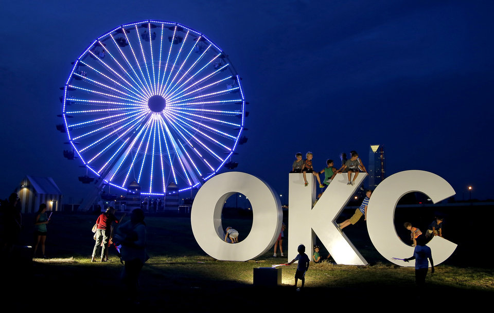 Photo - People play on an OKC sculpture in front of the Wheeler Ferris Wheel in Oklahoma City, Thursday, June 30, 2016. Photo by Bryan Terry, The Oklahoman