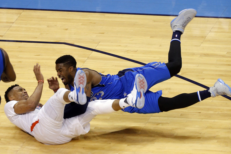 Photo - Oklahoma City's Russell Westbrook (0) and Dallas' Wesley Matthews (23) fall to the ground after getting tangled up during Game 2 in the first round of the NBA playoffs between the Oklahoma City Thunder and the Dallas Mavericks at Chesapeake Energy Arena in Oklahoma City, Monday, April 18, 2016. Photo by Sarah Phipps, The Oklahoman