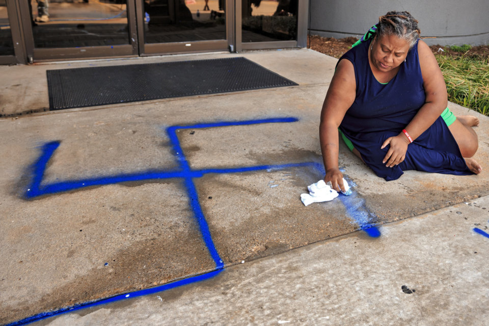 Photo - Oklahoma Black Lives Matter director Rev. Sheri Dickerson works to remove racist and homophobic symbols and language spray-painted on the building that includes the offices of the Oklahoma Democratic Party located at 3700 Classen Boulevard in Oklahoma City, Okla. on Thursday, March 28, 2019.  Photo by Chris Landsberger, The Oklahoman