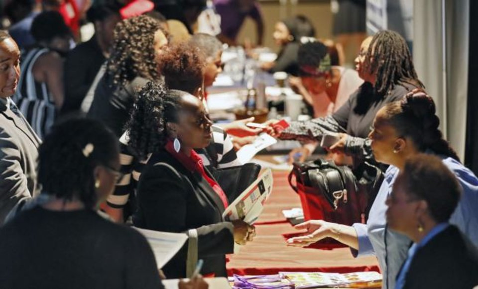 Photo -  Company representatives from Verizon, Goodwill, Kaiser Permanente and UPS, right, talk with potential applicants during a job and resource fair in Atlanta. [AP PHOTO]