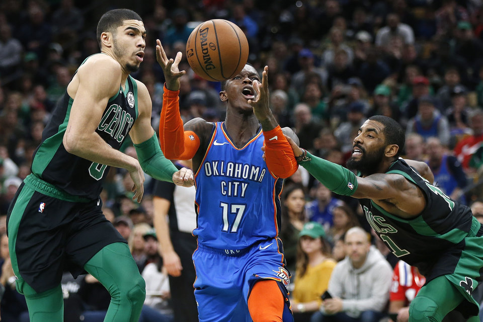 Photo - Oklahoma City Thunder's Dennis Schroder (17) drives for the basket between Boston Celtics' Jayson Tatum (0) and Kyrie Irving (11) during the second half of an NBA basketball game in Boston, Sunday, Feb. 3, 2019. (AP Photo/Michael Dwyer)