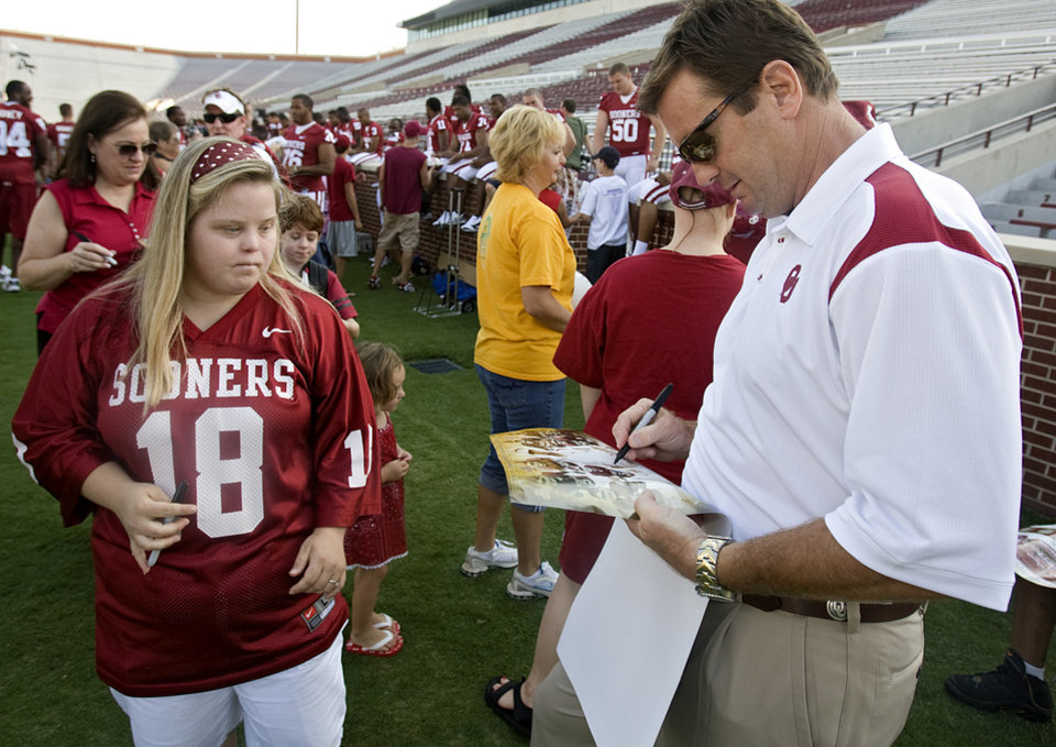 Photo - OU COLLEGE FOOTBALL: Head coach Bob Stoops signs a poster with his autograph for Heather Hancock during the University of Oklahoma (OU) media day at the Gaylord Family -- Oklahoma Memorial Stadium on Wednesday, Aug. 6, 2008, in Norman, Okla.  Staff Photo By CHRIS LANDSBERGER ORG XMIT: KOD