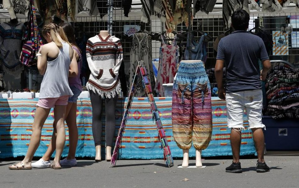 Photo - Patrons view items at temporary shops on Main Street during Norman Music Fest 2019 on April 27, 2019 in Norman, Okla.  [Steve Sisney/For The Oklahoman]