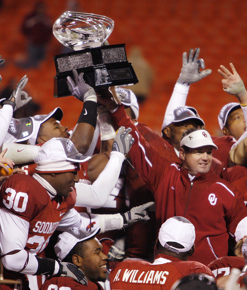 Photo - Bob Stoops and the Sooners hold up the championship trophy after the Big 12 Championship college football game between the University of Oklahoma Sooners (OU) and the University of Missouri Tigers (MU) on Saturday, Dec. 6, 2008, at Arrowhead Stadium in Kansas City, Mo.   PHOTO BY CHRIS LANDSBERGER/THE OKLAHOMAN  ORG XMIT: KOD