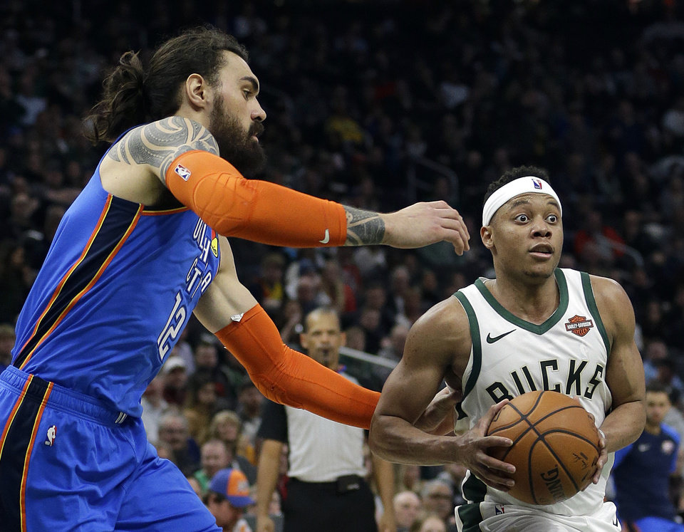 Photo - Milwaukee Bucks' Tim Frazier drives to the basket against Oklahoma City Thunder's Steven Adams during the second half of an NBA basketball game Wednesday, April 10, 2019, in Milwaukee. (AP Photo/Aaron Gash)