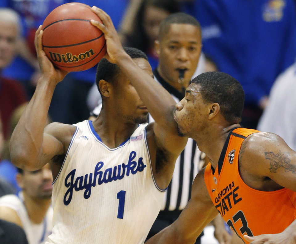 Photo - Oklahoma State guard Marcus Smart (33) is fouled by Kansas guard Wayne Selden, Jr. (1) during the second half of an NCAA college basketball game at Allen Fieldhouse in Lawrence, Kan., Saturday, Jan. 18, 2014. Kansas defeated Oklahoma State 80-78. (AP Photo/Orlin Wagner)