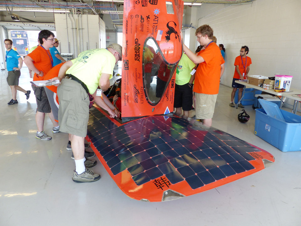 Photo -  Solar car No. 256 from Oregon State University gets work done at the electrical inspection station.   PROVIDED -