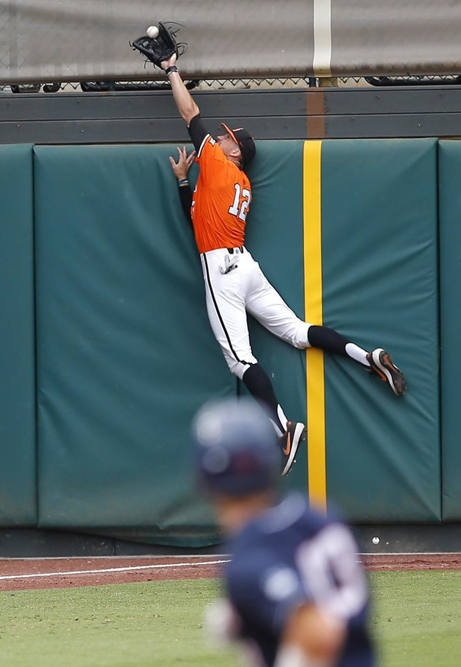 Photo - Oklahoma State's Carson McCusker (12) makes a catch against the wall in left field in the 1st inning during the Oklahoma City Regional NCAA baseball game between Oklahoma State University (OSU) and UConn at Chickasaw Bricktown Ballpark in Oklahoma City,  Monday, June 3, 2019. [Sarah Phipps/The Oklahoman]