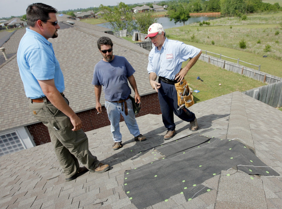 Photo - STORM DAMAGE: Jim Beres, right, and Allen Vollmer, middle, both with Good Guys Construction, show Eric Ingram, owner of Aegis Roofing, temporary roof repairs where Beres and Vollmer will later install a new chimney block on the roof at 2608 Southern Hills Drive in Moore, Oklahoma, Tuesday, May 11, 2010. The home was damaged in the severe weather the previous day. Photo by Nate Billings, The Oklahoman ORG XMIT: KOD
