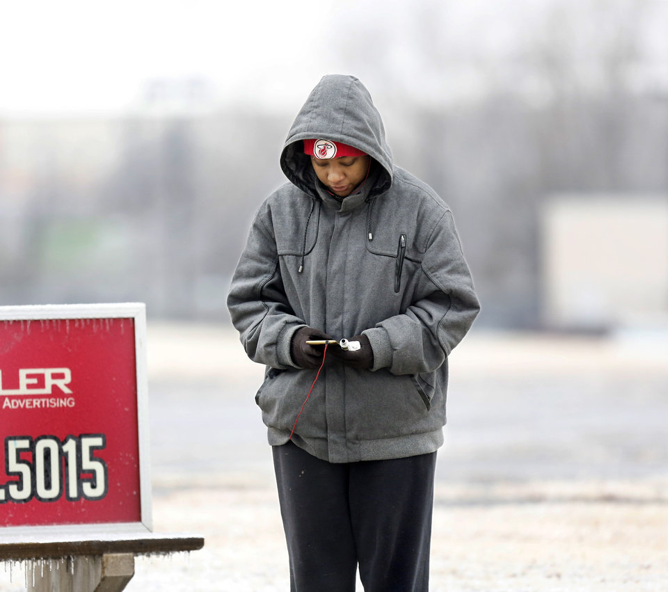 Photo - Standing in temperatures at or below freezing, Shay Brown is dressed for the weather as she waits to board an Embark city bus near NE 42 and Lincoln Blvd. Winter weather in the metro area on Thursday, Jan. 3, 2019.  Photo by Jim Beckel, The Oklahoman.