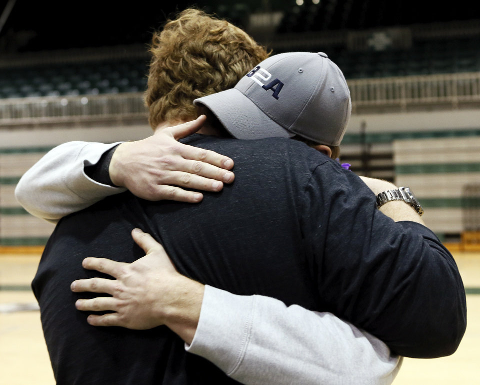 Photo - J.R. Hensley, back to camera, hugs older brother Ty Hensley after J.R. signed to play football at the University of Hawaii during a national signing day ceremony at Edmond Santa Fe High School in Edmond, Okla., Wednesday, Feb. 4, 2015. Ty Hensley also went to Edmond Santa Fe and is a Yankees prospect. Photo by Nate Billings, The Oklahoman