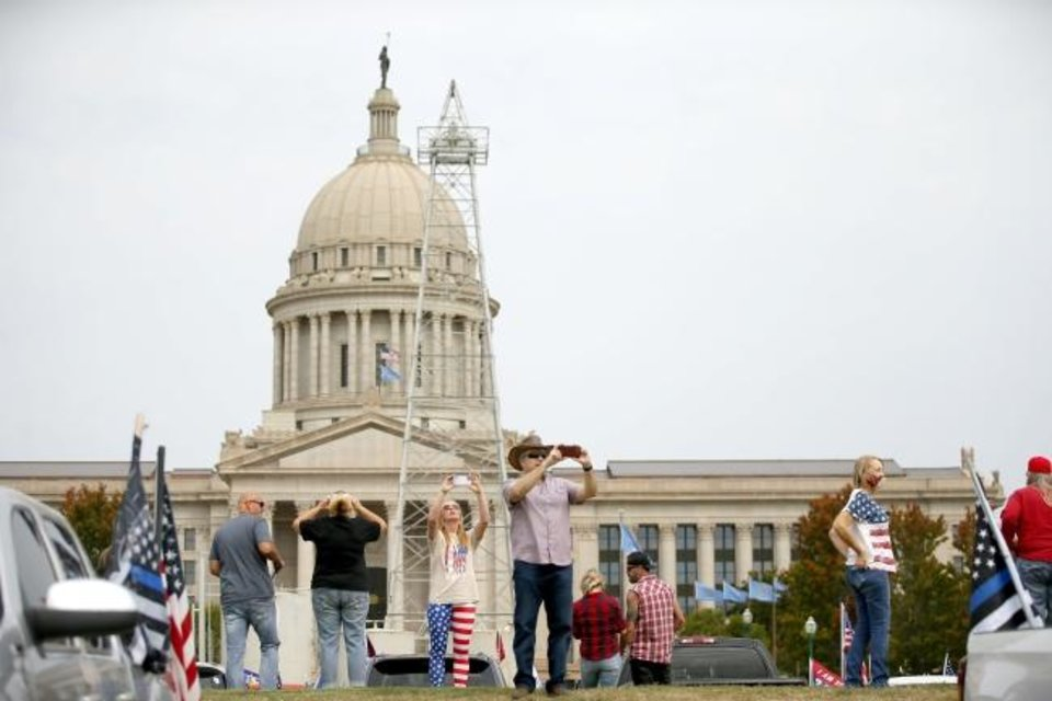 Photo -  President Donald Trump supporters take photos and video Saturday on the south side of the state Capitol during a MAGA DRAG the Interstate event. [Bryan Terry/The Oklahoman]