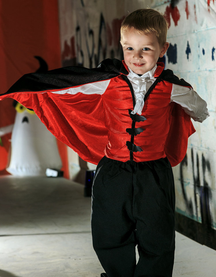 Photo - Colt makes a frighteningly cute vampire, but don't get too close!  This young creature of mythology will haunt the streets of your neighborhood in search of his favorite holiday treats. The outfit includes a vest with sleeves and an attached cape. Costume sold at Party Galaxy. Photo by Chris Landsberger, The Oklahoman  CHRIS LANDSBERGER