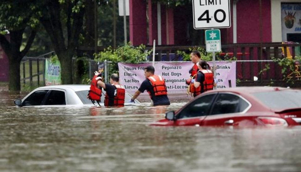 Photo -  Oklahoma City firefighters perform a high-water rescue Thursday morning when heavy rains overwhelmed stormwater drainage systems and caused flooded streets in Oklahoma City as another round of severe storms passes through the metro. [Jim Beckel/The Oklahoman]
