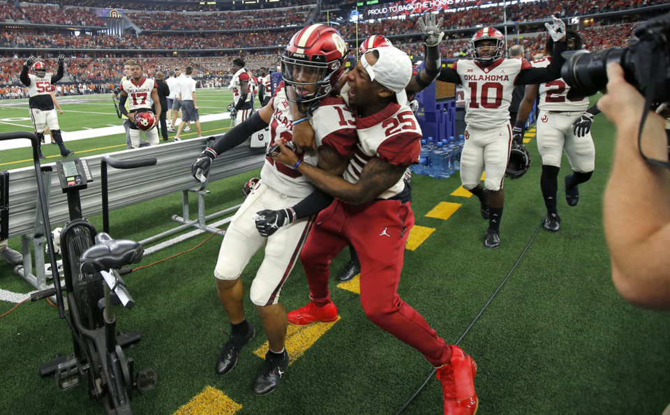 Photo - Oklahoma's Tre Norwood (13) celebrates with Justin Broiles (25) after Norwood intercepted a pass late in the Big 12 Championship football game between the Oklahoma Sooners (OU) and the Texas Longhorns (UT) at AT&T Stadium in Arlington, Texas, Saturday, Dec. 1, 2018.  Oklahoma won 39-27. Photo by Bryan Terry, The Oklahoman