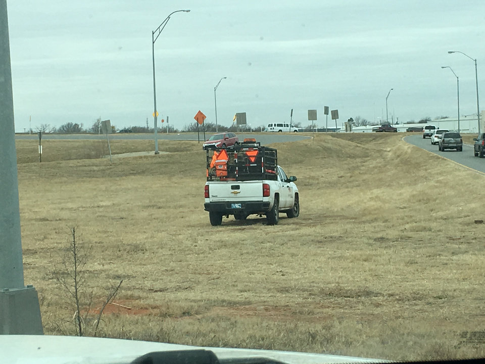 Photo -  Crews pick up trash along the roadway in Oklahoma City. [PHOTO BY MATT PATTERSON, THE OKLAHOMAN]