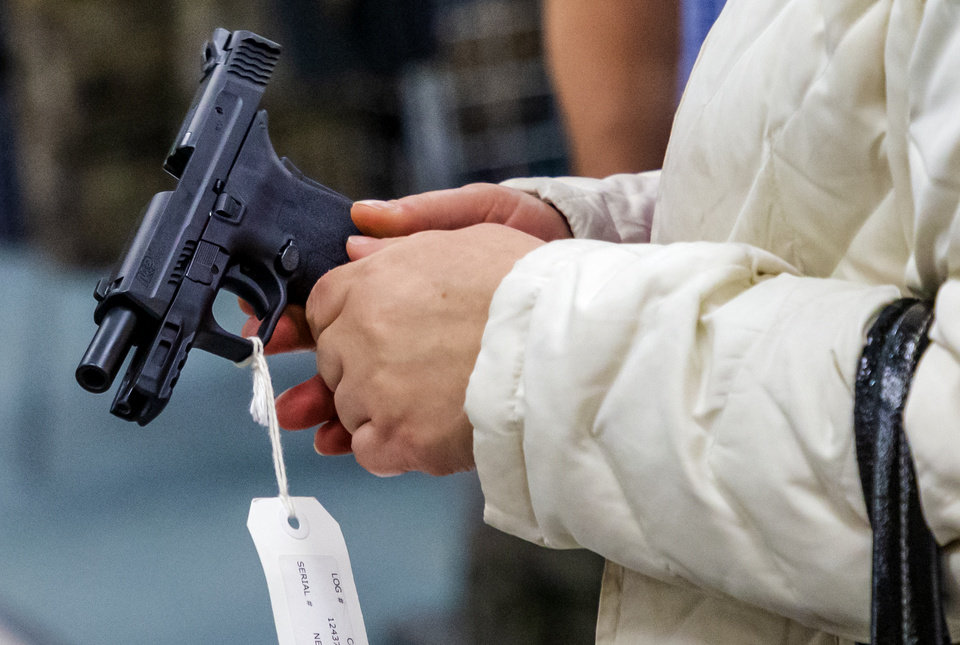 Photo - A customers takes a closer look at a handgun at H&H Shooting Sports in Oklahoma City, Okla. on Wednesday, March 18, 2020.  [Chris Landsberger/The Oklahoman]