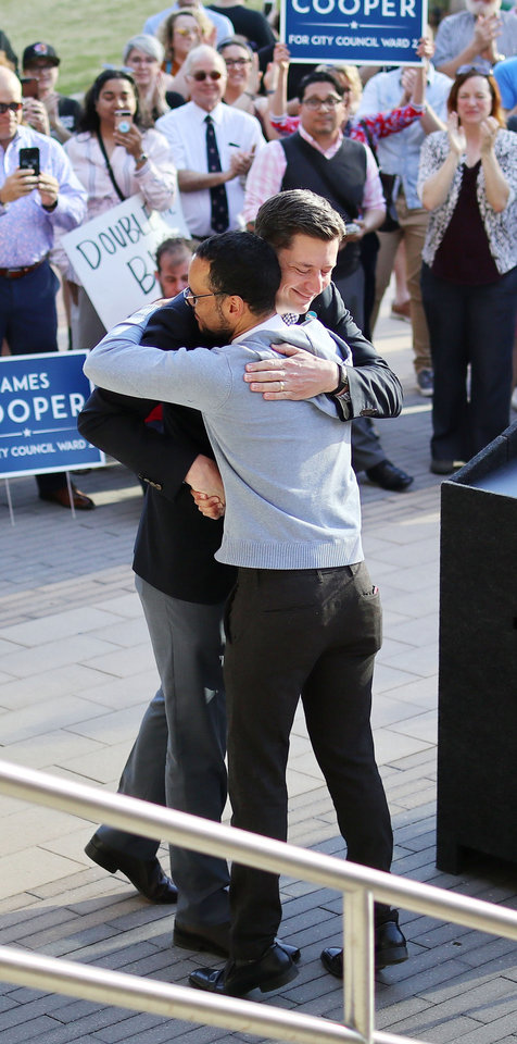 Photo - Mayor David Holt hugs James Cooper at the podium after introducing him. Marchers join councilman-elect James Cooper in a march from Main and Broadway to City Hall in support of the LGBTQ community, Monday, April 8, 2019.  Photo by Doug Hoke/The Oklahoman
