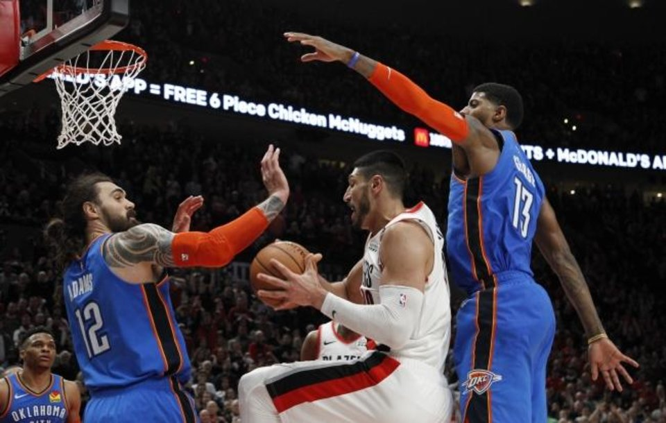 Photo -  Portland Trail Blazers center Enes Kanter, center, grabs a rebound as Oklahoma City Thunder center Steven Adams, front left, and Thunder forward Paul George, right, defend during the second half of Game 1 of a first-round NBA basketball playoff series in Portland, Ore., Sunday, April 14, 2019. (AP Photo/Steve Dipaola)