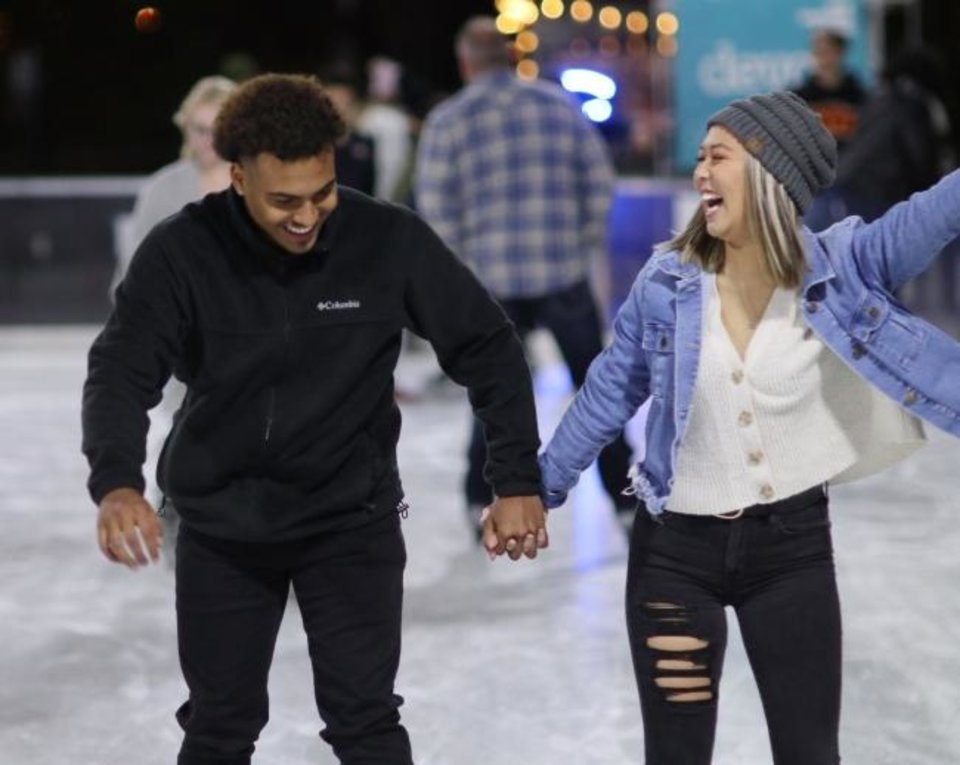 Photo -  Keylan Murray and Tiffany Bui skate on Nov. 8, the opening day of the Devon Ice Rink on the seasonal plaza of the Myriad Botanical Gardens. The ice rink is part of Downtown in December. [Doug Hoke/The Oklahoman]