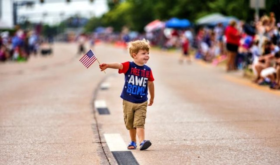 Photo -  Finn Emerich, 3, walks down the street waving his American flag to those awaiting the start of the Bethany Freedom Festival parade.    [Chris Landsberger/The Oklahoman]