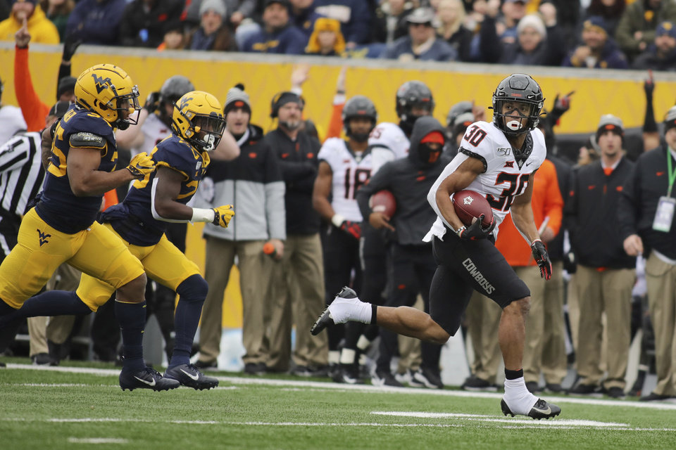 Photo - Oklahoma State running back Chuba Hubbard (30) looks down field on a long run against West Virginia the first half of an NCAA college football game in Morgantown, W.Va., on Saturday, Nov. 23, 2019. (AP Photo/Chris Jackson)