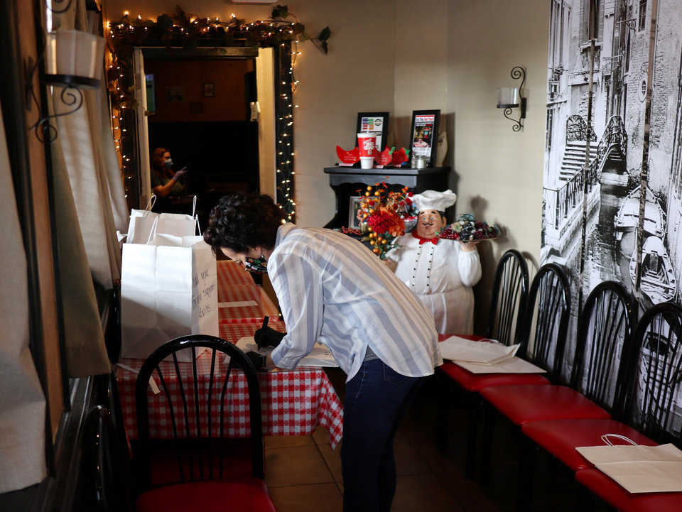 Photo - Owner Cathy Cummings writes a personal note on each order. Vito's Ristorante will continue to have carry out even after the dining room opens because of the limits in the number of customers allowed to dine in at once. Wednesday, May 13, 2020. [Doug Hoke/The Oklahoman]