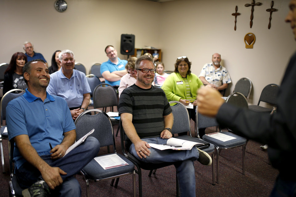 Photo -  John Wiggs, left, and Chad Drewery laugh from the front row as Doug Weeks speaks during a Moore Toastmasters meeting. [PHOTOs BY BRYAN TERRY, THE OKLAHOMAN]