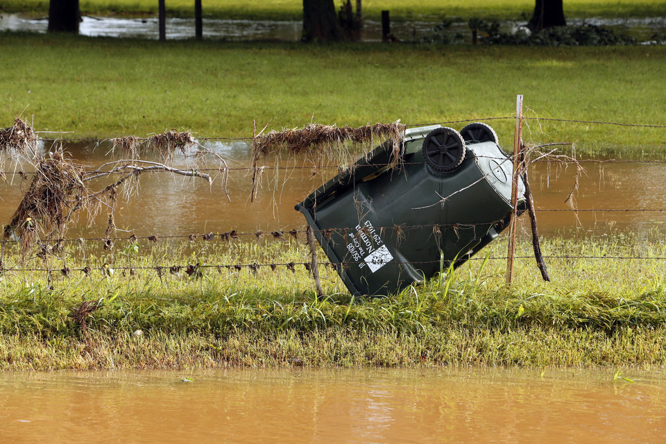 Photo - Debris washed against the fence on Franklin road on Saturday, June 1, 2013 in Norman, Okla.  illustrates the level of flood water damage after Friday night's storm.  Photo by Steve Sisney, The Oklahoman
