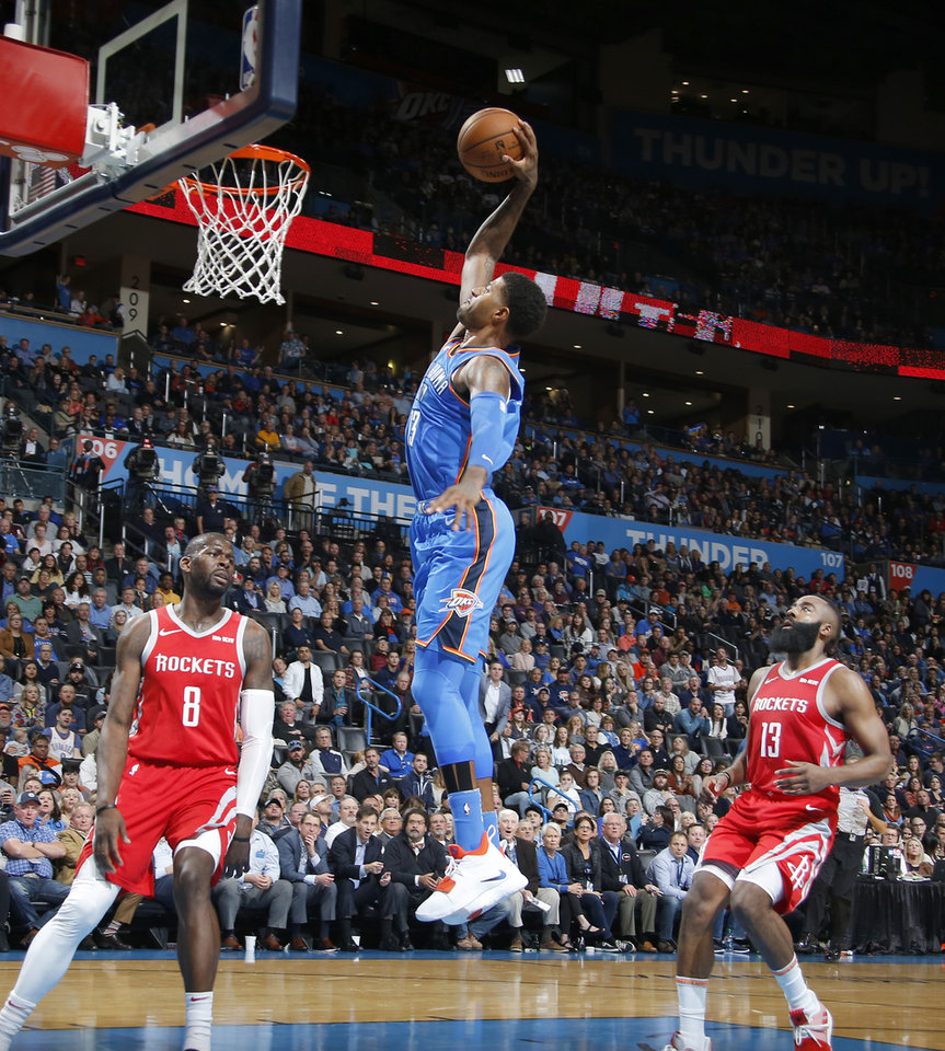 283596b92f2 Oklahoma City s Paul George (13) goes to the basket between Houston s James  Ennis III (8) and James Harden (13) after a foul during an NBA basketball  game ...