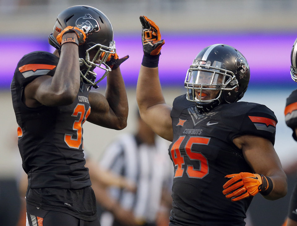 Photo - Oklahoma State's Tre Flowers (31) and Chad Whitener (45) celebrate a Flowers interception during the college football game between the Oklahoma State Cowboys (OSU) and TCU Horned Frogs at Boone Pickens Stadium in Stillwater, Okla., Saturday, Nov. 7, 2015. Photo by Sarah Phipps, The Oklahoman