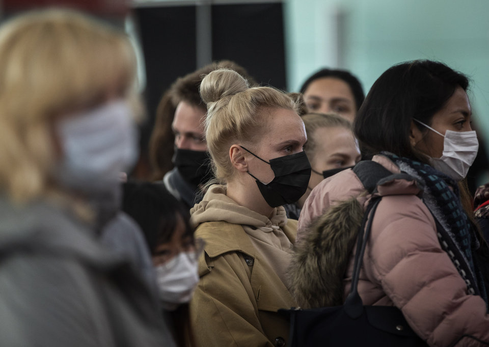 Photo -  Passengers wearing masks line up as they wait to check in at Barcelona airport, Spain, Saturday, March 14, 2020. Spain's prime minister has announced a two-week state of emergency from Saturday in a bid to contain the new coronavirus outbreak. For most people, the new coronavirus causes only mild or moderate symptoms. For some, it can cause more severe illness, especially in older adults and people with existing health problems. (AP Photo/Emilio Morenatti)