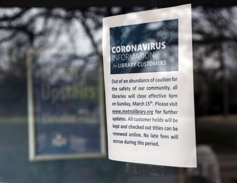 Photo - A sign on an entrance to the Belle Isle Library, 5501 N Villa Ave., says the library is closed because of the coronavirus pandemic, in Oklahoma City, Monday, March 16, 2020. The Metropolitan Library System is closed for at least two week. [Nate Billings/The Oklahoman]