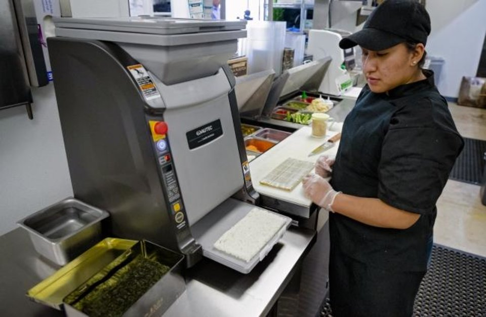 Photo -  Employee Julie Lopez gets a bed of rice as she uses the new automated Maki Maker while making a sushi roll at the new Nhinjo Sushi-Grill.  [Chris Landsberger/The Oklahoman]