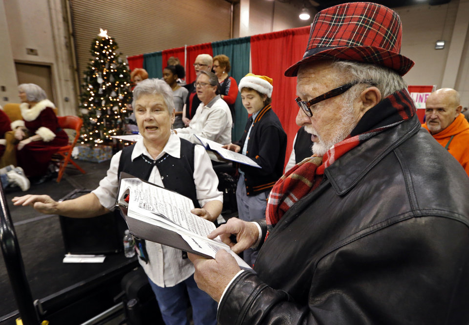 Photo -  Oklahoma City Community Choir members Sharron Clifton and Dwayne Conts sing carols Monday during the Red Andrews Christmas Dinner. [Photo by Steve Sisney, The Oklahoman]