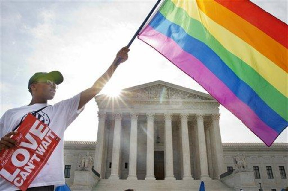 Photo - Carlos McKnight of Washington, waves a flag in support of gay marriage outside of the Supreme Court in Washington, Friday June 26, 2015. A major opinion on gay marriage is among the remaining to be released before the term ends at the end of June.  (AP Photo/Jacquelyn Martin)