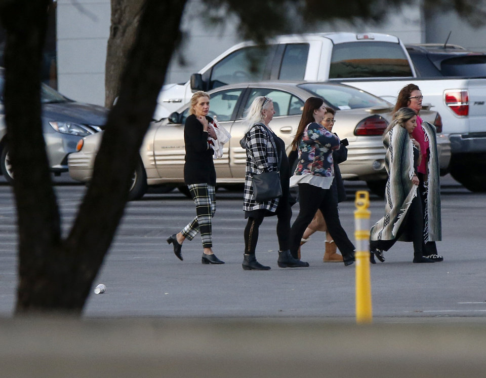 Photo - People walk through the parking lot on the south side of Penn Square Mall after a shooting inside the mall in Oklahoma City, Thursday, Dec. 19, 2019. [Nate Billings/The Oklahoman]