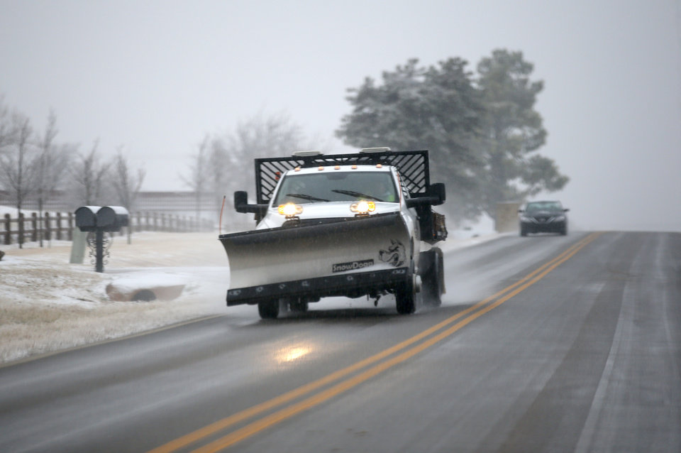 Photo - A snow plow travels east on Covell Road in Edmond, Okla.,   Thursday, Jan. 3, 2019. Photo by Sarah Phipps, The Oklahoman