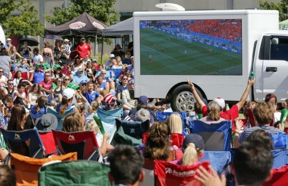 Photo -  People watch in the FIFA Women's World Cup game between the U.S. Women's National Team and the Netherlands on truck-mounted TVs provided by the OKC Energy FC at Together Square. [Nate Billings/The Oklahoman]