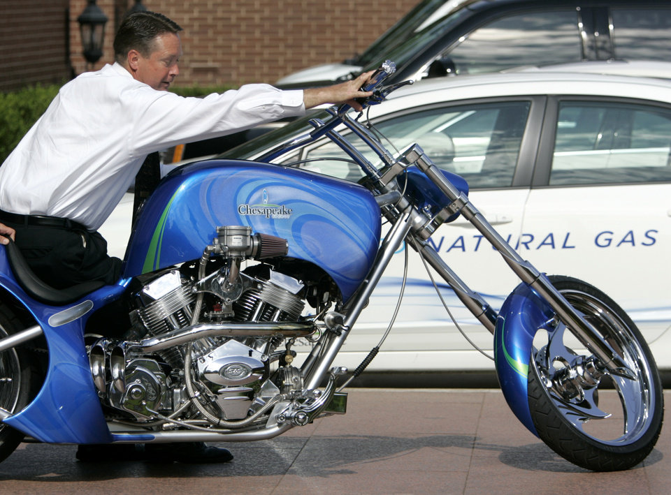 Photo - COMPRESSED NATURAL GAS / MOTORCYCLE: Fleet NGV Specialist Mark Harris pushes the Chesapeake CNG Chopper on the sidewalk of the Chesapeake campus in Oklahoma City, June 15, 2009.  Photo by Steve Gooch, The Oklahoman ORG XMIT: KOD