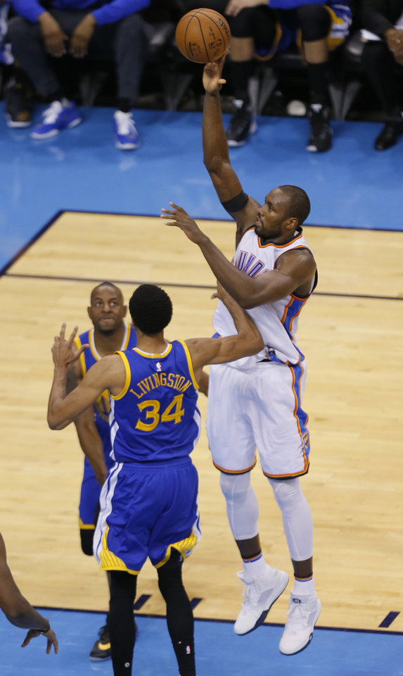 Photo - Oklahoma City's Serge Ibaka (9) shoots over Golden State 's Shaun Livingston (34) during Game 3 of the Western Conference finals in the NBA playoffs between the Oklahoma City Thunder and the Golden State Warriors at Chesapeake Energy Arena in Oklahoma City, Sunday, May 22, 2016. Photo by Sarah Phipps, The Oklahoman