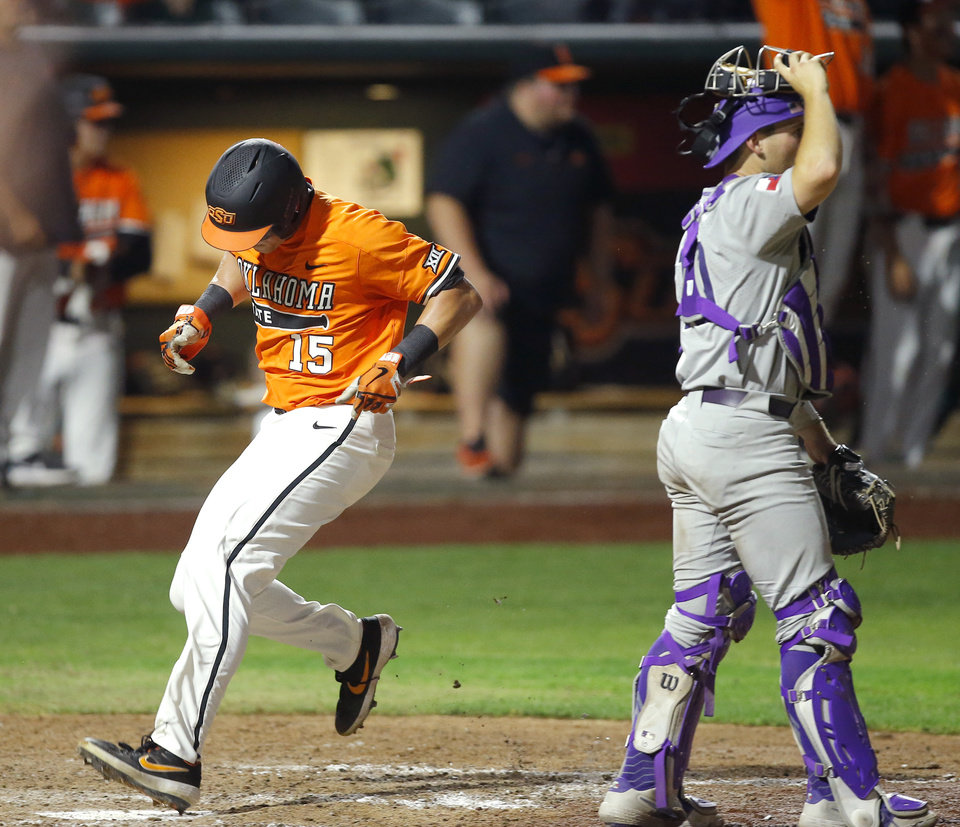 Photo - Oklahoma State's Cade Cabbiness (15) scores past TCU's Zach Humphreys (10) in the sixth inning of a Big 12 baseball tournament game between Oklahoma State University (OSU) and TCU at Chickasaw Bricktown Ballpark in Oklahoma City, Okla., Wednesday, May 22, 2019.  [Bryan Terry/The Oklahoman]
