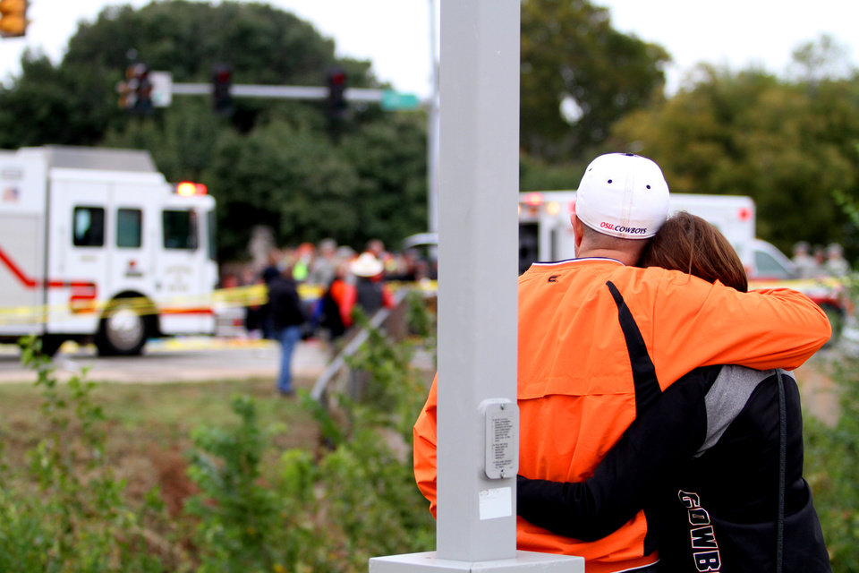 Photo - Chris and Davedda Marshall, from The Woodlands, Texas, console each other. An accident occurred at the intersection of Hall of Fame and Main during the OSU homecoming parade on Oct. 24 in Stillwater, Oklahoma. Photo by Kurt Steiss, For the Oklahoman