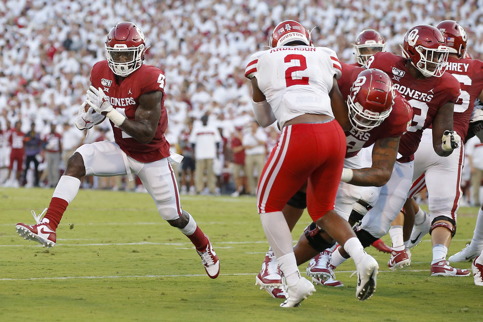 Photo - Oklahoma's Trey Sermon (4) carries the ball during a college football game between the University of Oklahoma Sooners (OU) and the Houston Cougars at Gaylord Family-Oklahoma Memorial Stadium in Norman, Okla., Sunday, Sept. 1, 2019. Oklahoma won 49-31. [Bryan Terry/The Oklahoman]