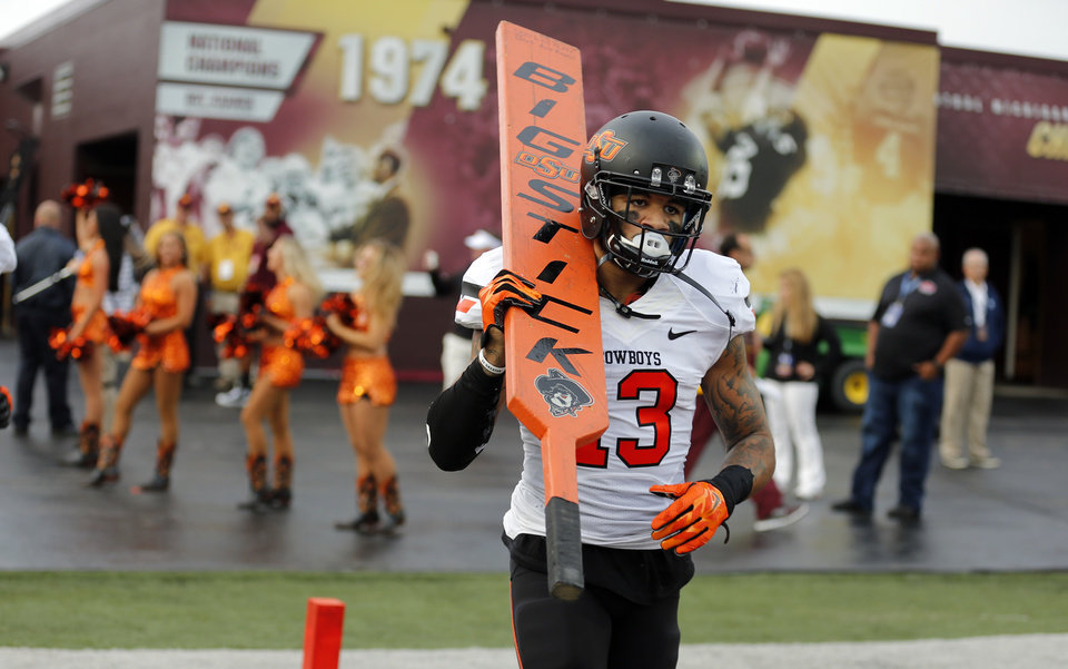 "Photo - Oklahoma State's Jordan Sterns (13) carries the ""Big Stick"" before the college football game between the Central Michigan Chippewas and the Oklahoma State University Cowboys at the Kelly/Shorts Stadium in Mount Pleasant, Mich., Thursday, Sept. 3, 2015. Photo by Sarah Phipps, The Oklahoman"