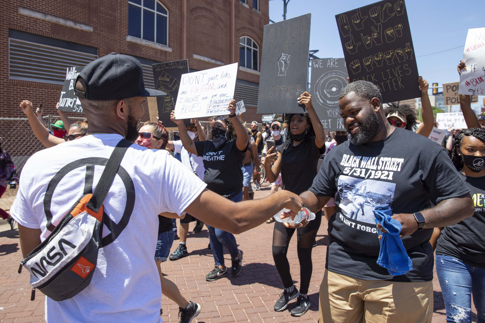 Photo - A protester is handed a water during a Black Lives Matter OKC Rally in the Bricktown area of Oklahoma City on a hot Saturday, June 6, 2020. Photo by Alonzo Adams for The Oklahoman.